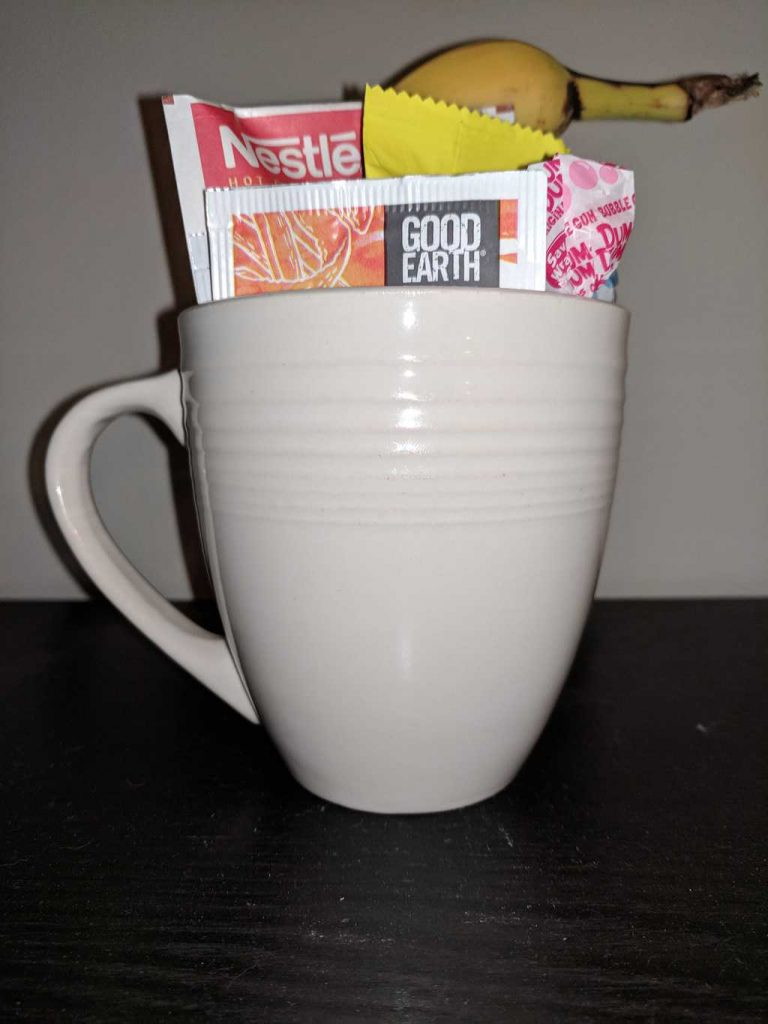 banana, protein bar, lollipops, hot cocoa mix, tea in a white mug on a brown table