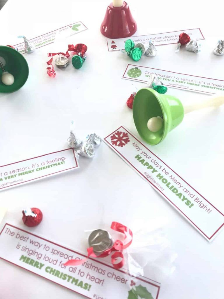 red and green bells, hersheys kisses and strips of paper with various encouraging Christmas phrases on them on a white background