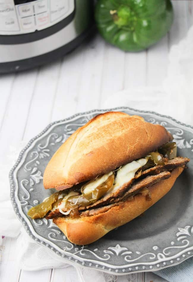 philly cheesesteak sandwich on a gray plate with an instant pot and green bell pepper in the background, all on a white wood table
