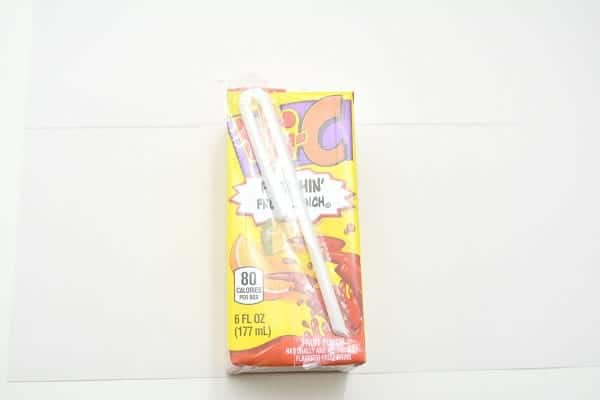 a juice box on a white paper with a line drawn on the paper