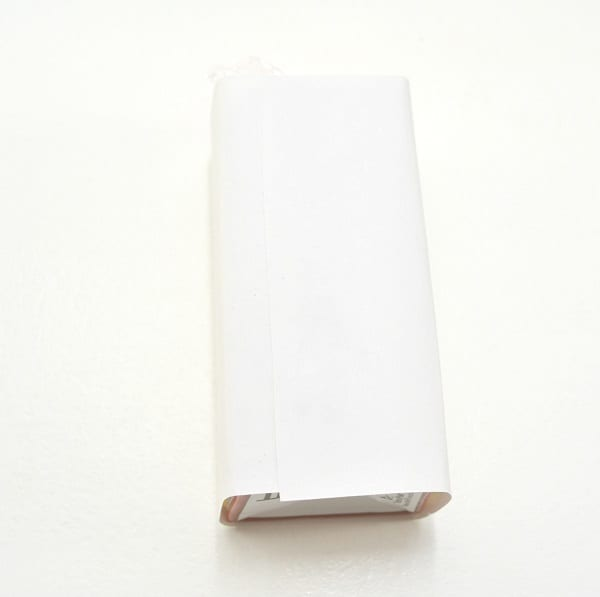 white paper wrapped around a juice box on a white background