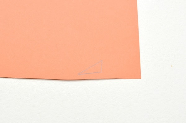 a triangle drawn on a piece of orange construction paper on a white background