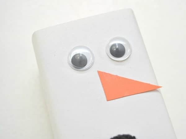 a juice box wrapped with white paper with two googly eyes and an orange paper triangle nose on it on a white background