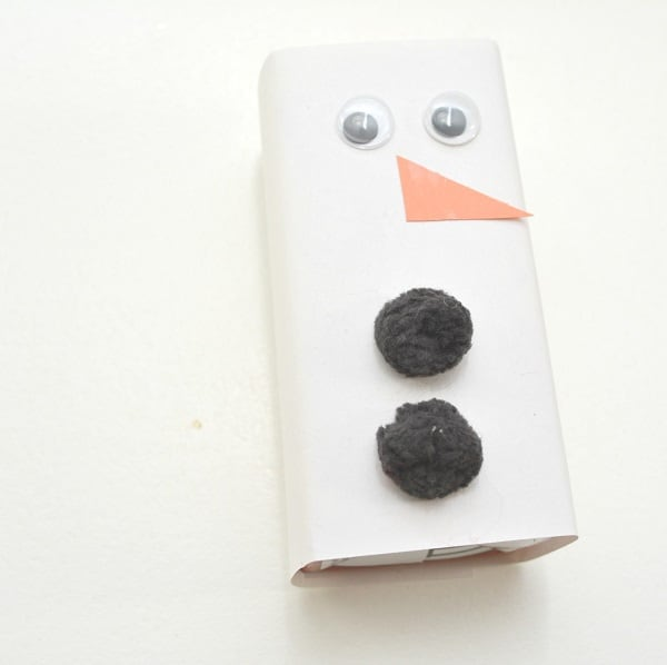 a juice box wrapped with white paper with two googly eyes, an orange paper triangle nose and two black pom poms on it to look like a snowman on a white background