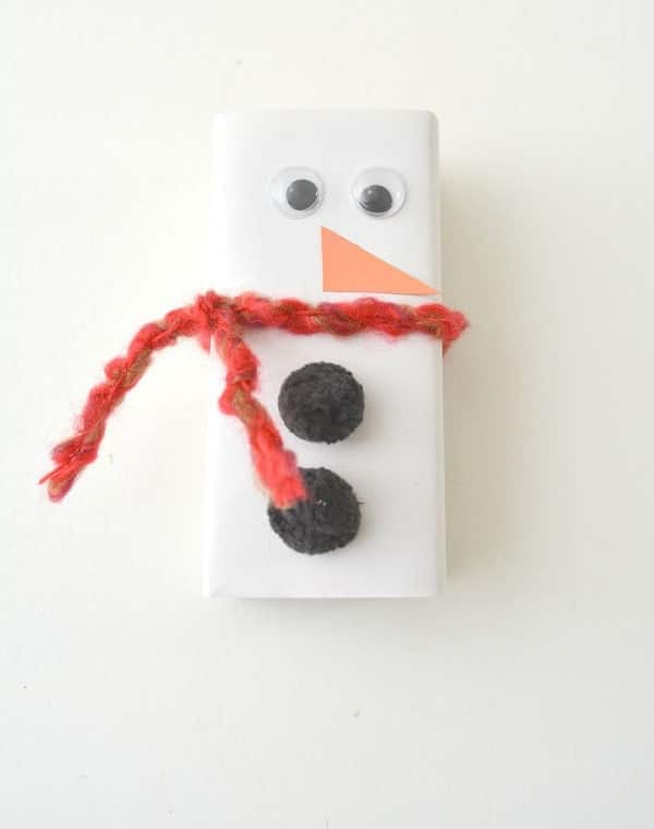 a juice box wrapped in white paper and decorated with googly eyes, orange paper nose, red yarn scarf, black pom poms as buttons to look like a snowman on a white background