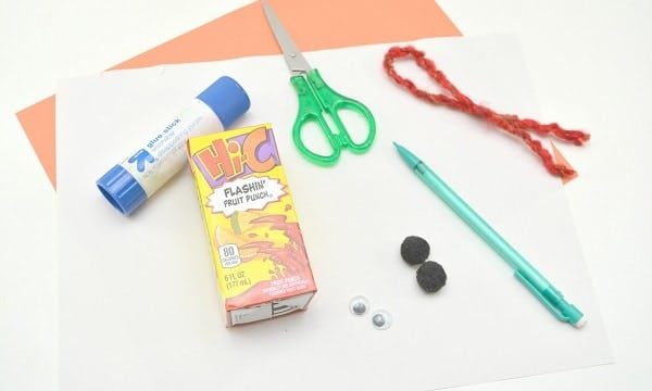 white and orange construction paper, a glue stick, 2 small black pom poms, 2 googly eyes, scissors, red yarn and a juice box.