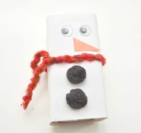 a juice box wrapped with white paper, with googly eyes, an orange paper nose, red yarn scarf and black pom pom buttons to look like a snowman on a white background