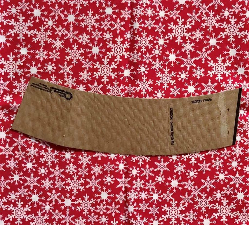 a cardboard hand protector on red fabric with white snowflakes on it