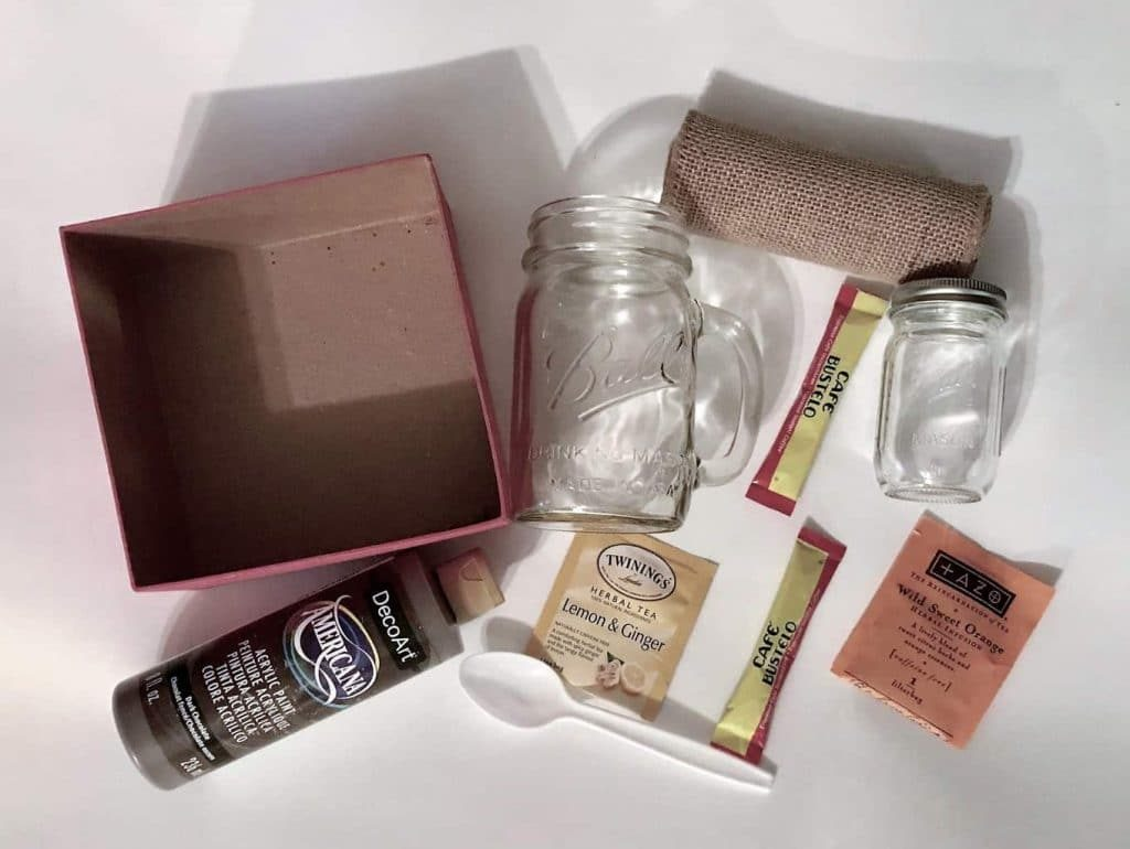 a cardboard box, mason jar, another jar, roll of burlap, packets of coffee and tea, a white plastic spoon, brown paint all on a white background