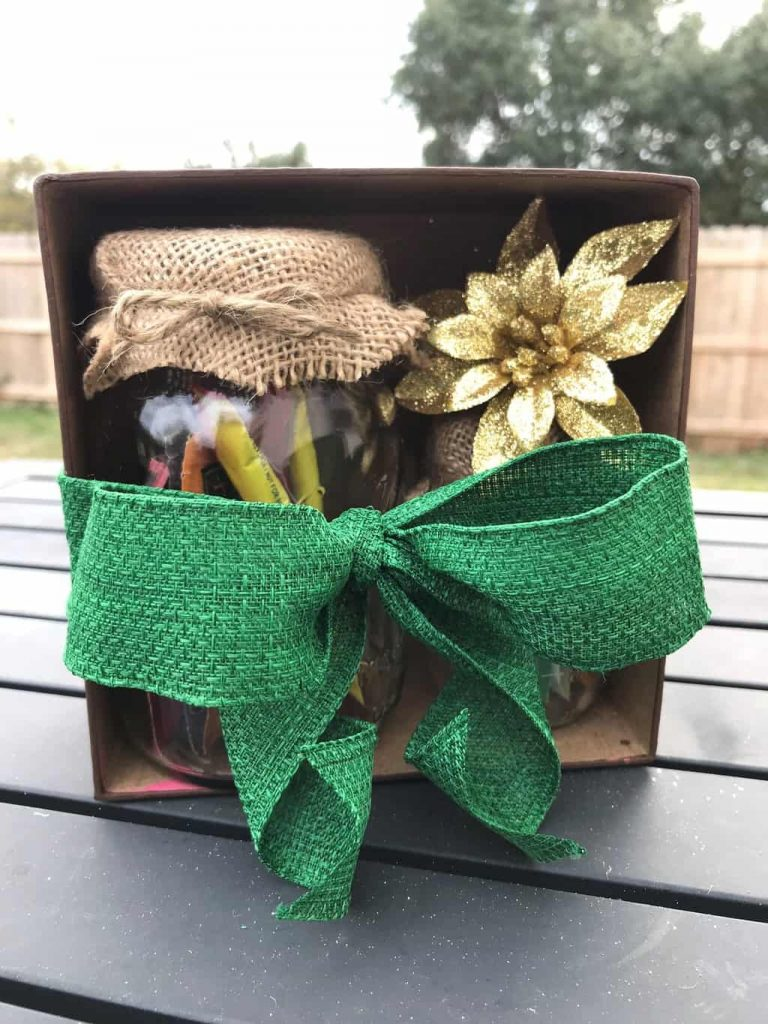 two glass jars topped with burlap or a gold bow in a cardboard box wrapped with a green bow on a brown table outside
