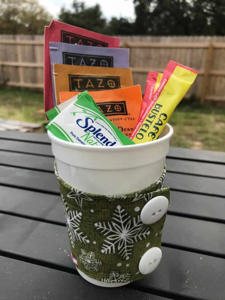 packets of tea, coffee and splenda in a white plastic cup wrapped in a green fabric with snowflakes and two white buttons on it on a brown table outside