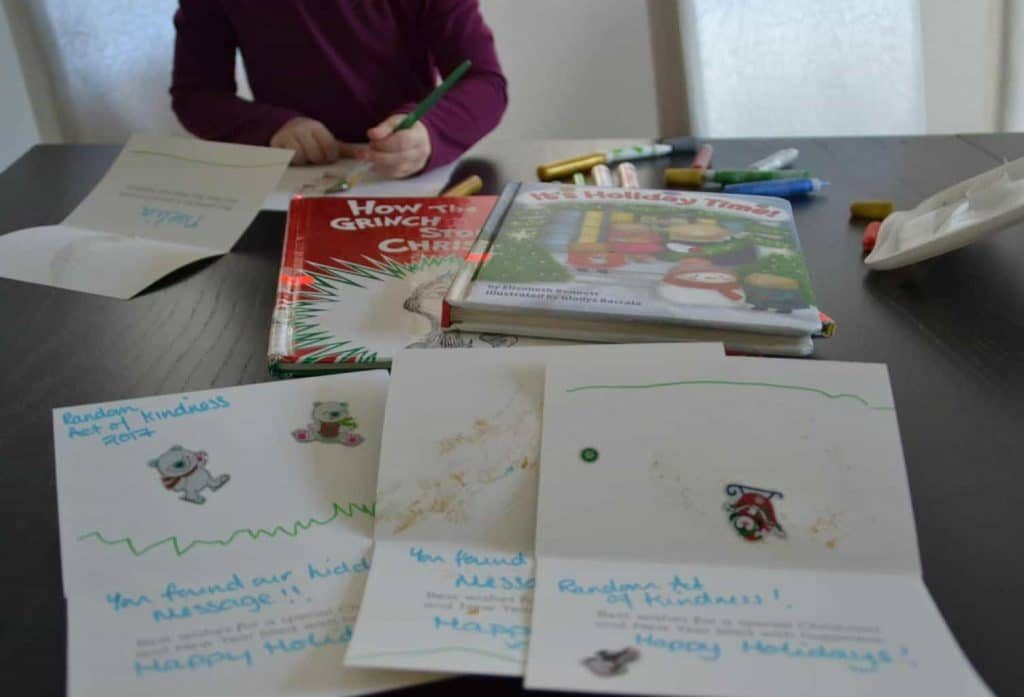 several Christmas Library Letters, books and markers on the table with a child holding a marker writing in one of the cards, all on a brown table