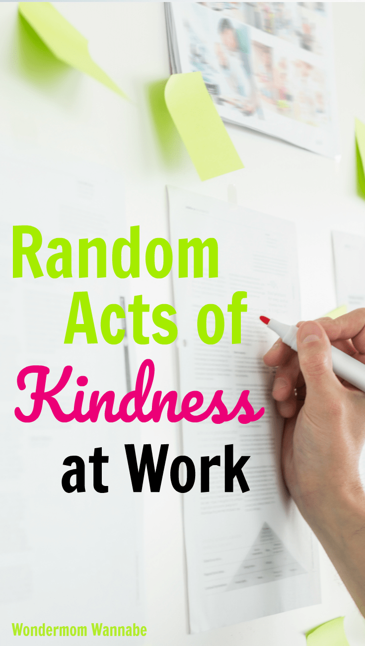 a hand writing on a piece of paper on a white board with other papers and sticky notes also on the board with title text reading Random Acts of Kindness at Work