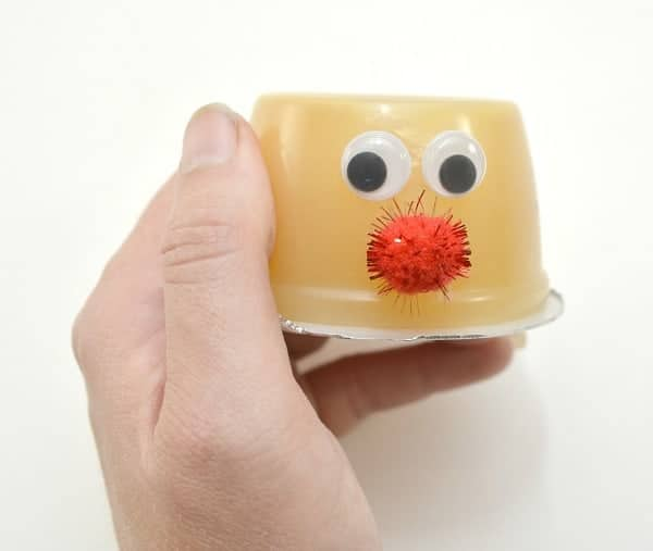 a hand holding an upside down applesauce cup with googly eyes and a red pom pom, as a nose, on it on a white background