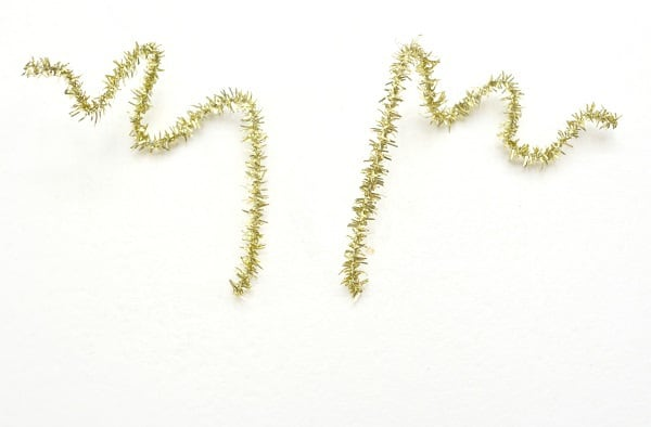 a gold pipe cleaner cut in half and shaped to look like antlers on a white background
