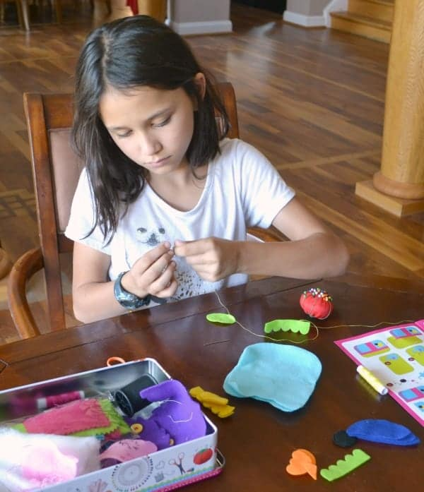 a girl sitting at a table using her sewing kit