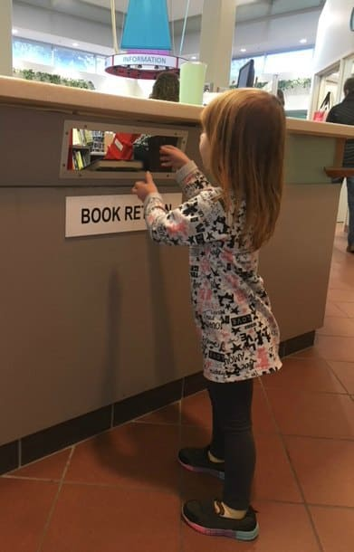 a child putting a book in the book return slot in a library