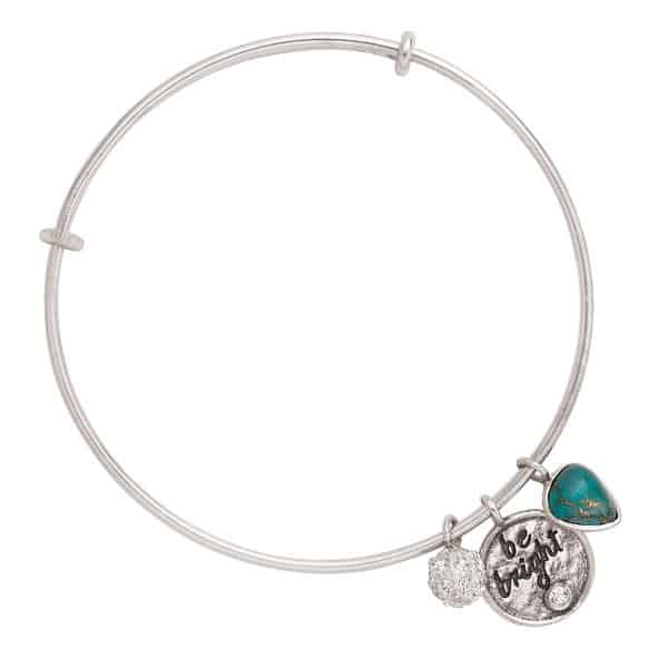 a silver bracelet with an emerald charm, a charm with text be bright, and  a diamond charm