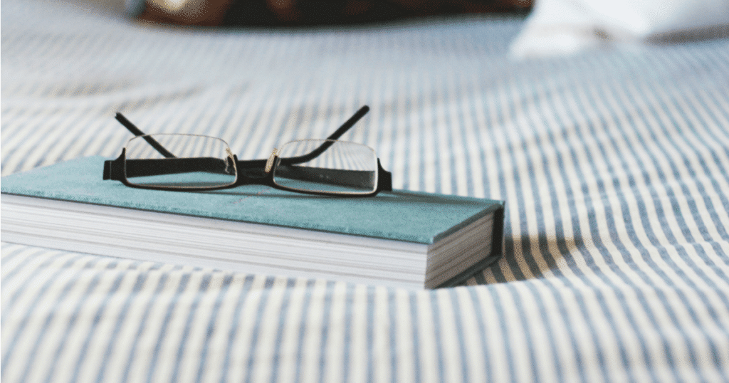 glasses on top of a book on a bed