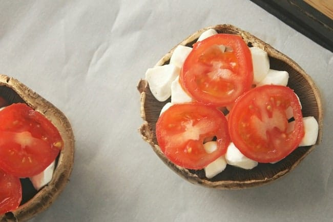 Caprese Stuffed Portobello Mushrooms on parchment paper on a baking sheet before being cooked