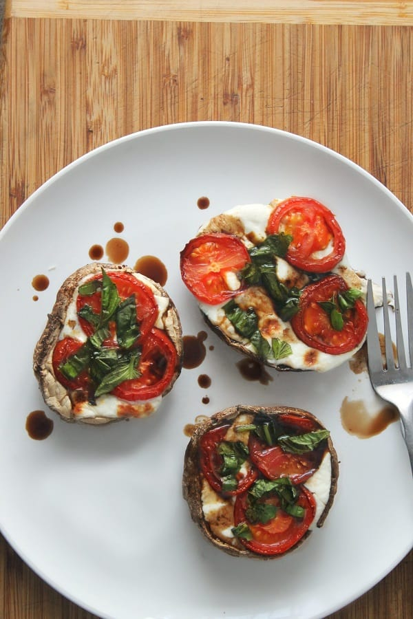 overhead view of three caprese stuffed portobello mushrooms on a white plate with a fork on it, on a brown table