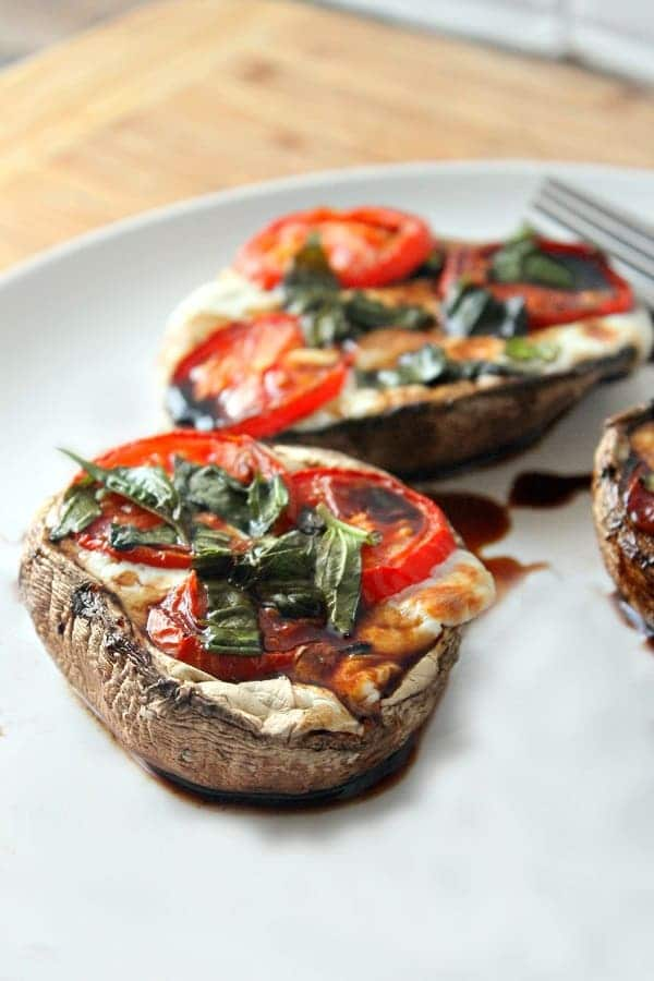 three caprese stuffed portobello mushrooms on a white plate with a fork on it, on a brown table