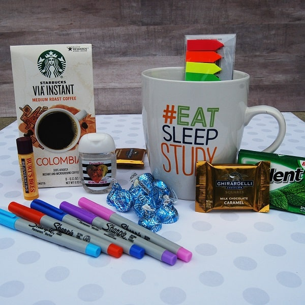 gum, hand sanitizer, chapstick, chocolate, coffee, colored tabs in a mug with text that reads #eat sleep study, highlighters on a white background