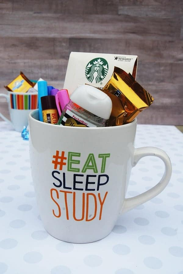 a mug with the words #eat sleep study on it full of hand sanitizer, highlighters, chapstick, coffee and chocolate on a white paper with another mug in the background
