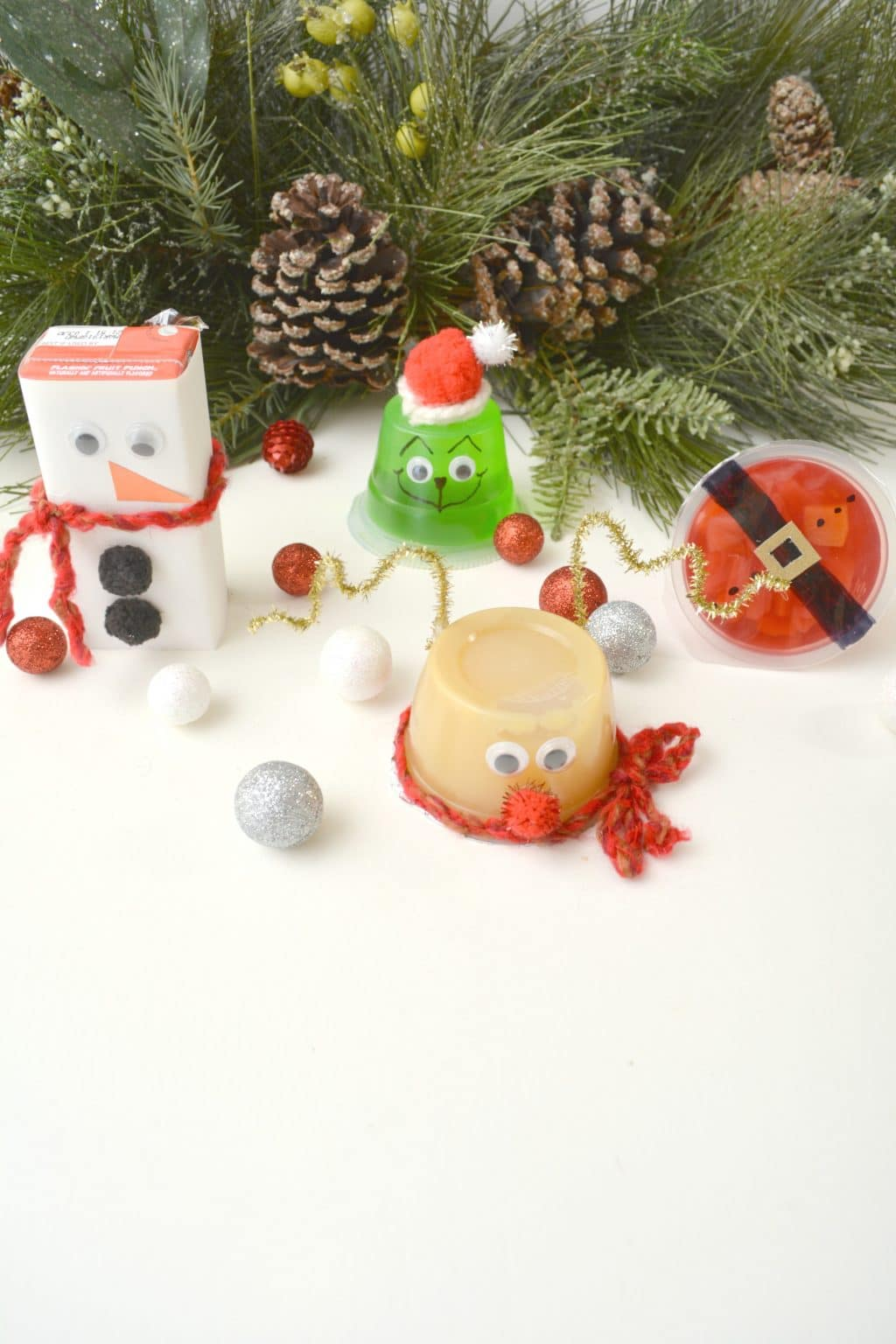 reindeer applesauce cup, grinch jello cup, juice box snowman, santa fruit cup on a white table with pine cones and tree branches behind them and silver, white and red styrofoam balls around them