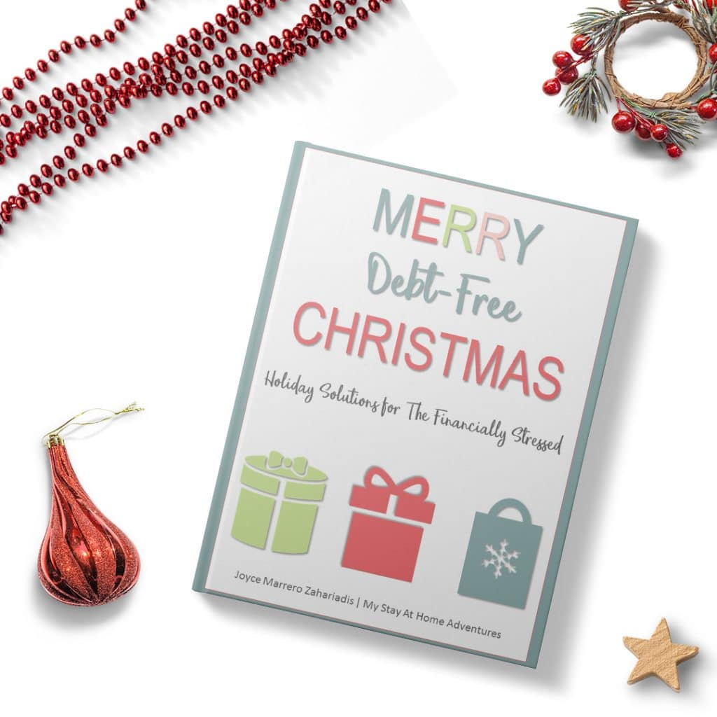 a book titled Merry Debt-Free Christmas Holiday Solutions for the Financially Stressed on a white background next to red beads, red holly mini wreath, wood star and red ornament