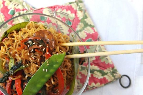teriyaki veggie stir fry and chopsticks in a glass bowl on a red flowered cloth