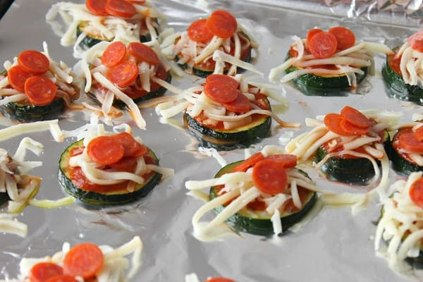 zucchini pizza bites on a foil lined baking sheet