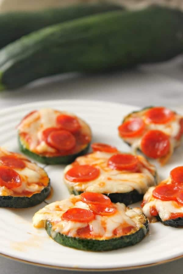 zucchini pizza bites on a white plate with zucchini in the background