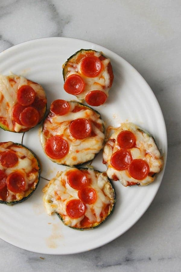 zucchini pizza bites on a white plate on a counter