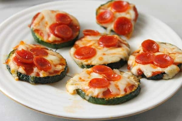 zucchini pizza bites, zucchini topped with cheese, sauce and pepperoni on a white plate