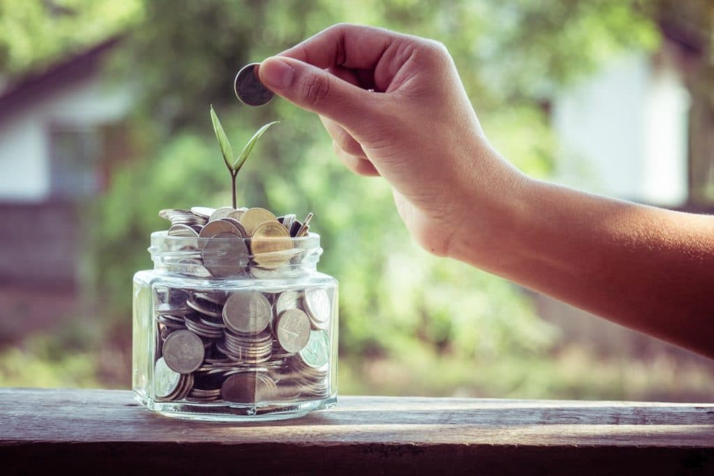 a hand placing a coin into a glass jar full of coins with a plant coming out of it on a wooden rail with trees and a house in the background