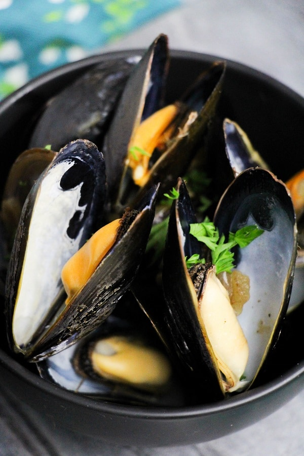 mussels in a black bowl on a wood board