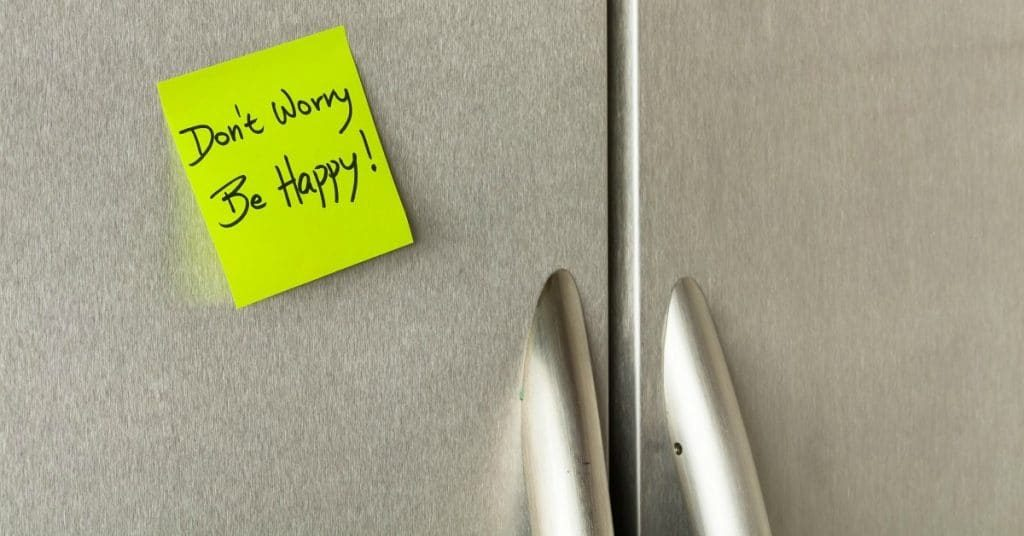 cabinet doors with a stick note on them reading Don'ts Worry Be Happy!