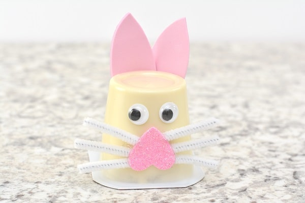 an upside down vanilla pudding cup with two googly eyes and an upside down pink foam heart on it with white pipe cleaner pieces as whiskers and pink foam cut to look like bunny ears on a gray counter