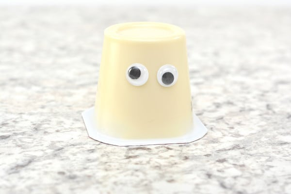 an upside down vanilla pudding cup with two googly eyes on it on a gray counter