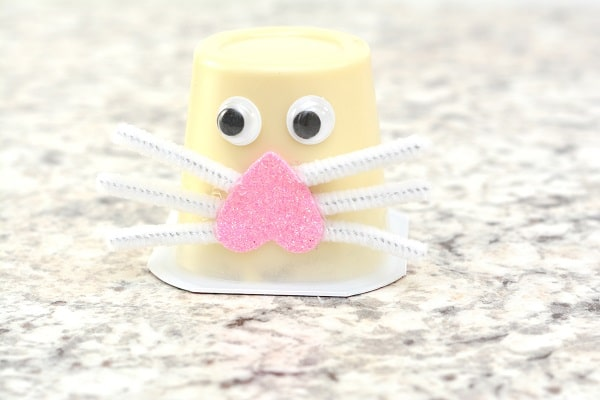 an upside down vanilla pudding cup with two googly eyes and an upside down pink foam heart on it with white pipe cleaner pieces as whiskers on a gray counter