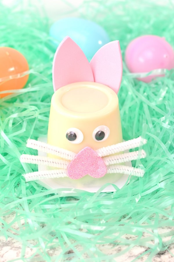 an upside down vanilla pudding cup decorated with pink foam, white pipe cleaners and googly eyes to look like a bunny on fake grass next to plastic eggs