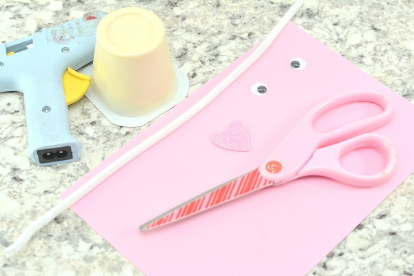 hot glue gun, vanilla pudding cup, white pipe cleaner, googly eyes, pink foam heart, sheet of pink foam, and pink scissors on a gray counter
