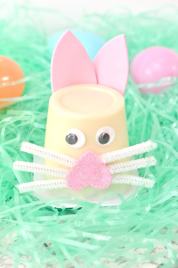 an upside down vanilla pudding cup with two googly eyes and an upside down pink foam heart on it with white pipe cleaner pieces as whiskers and pink foam cut to look like bunny ears on fake green grass with colored plastic eggs behind it