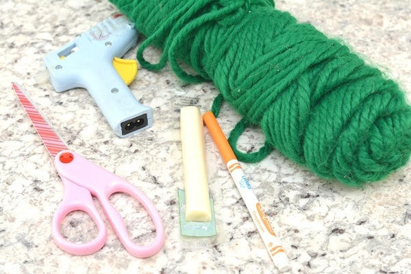 green yarn, an orange marker, scissors, a low-temperature glue gun, and a cheese stick on a gray counter