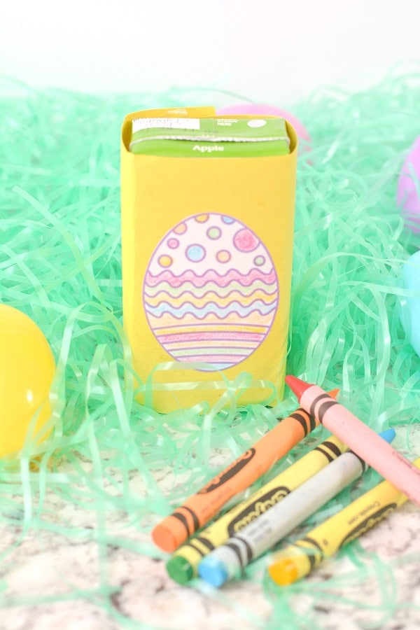 a juice box decorated wrapped in yellow paper with a paper egg glued on it on fake grass next to plastic eggs and crayons