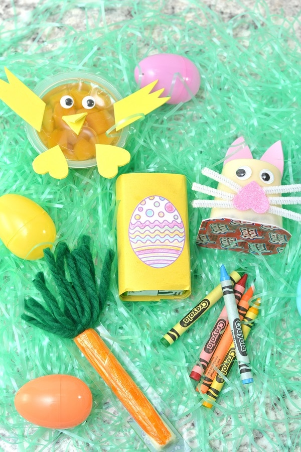a fruit cup, pudding cup, juice box and cheese stick decorated with paper, yarn, and pipe cleaners to look like a chick, bunny, egg, and carrot stick, all on fake grass next to plastic eggs and crayons