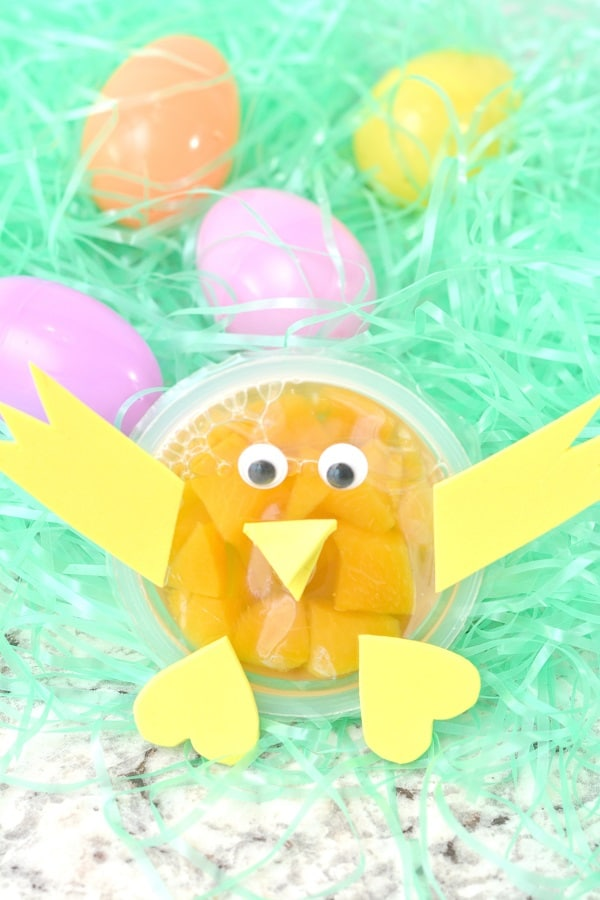 a fruit cup decorated with yellow paper and googly eyes to look like a chick on fake grass next to plastic eggs