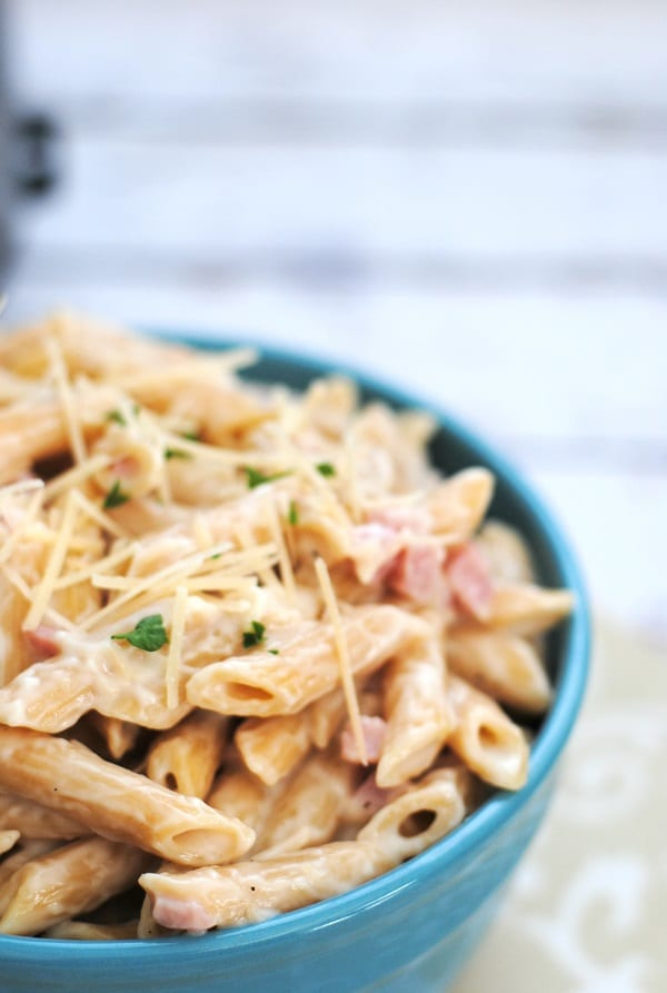 close up view of ham alfredo in a blue bowl on a tan and white cloth on a wood table