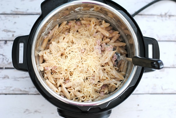 penne pasta, alfredo sauce, ham, mozzarella, and parmesan with a spoon in it, in an instant pot on a white wood table
